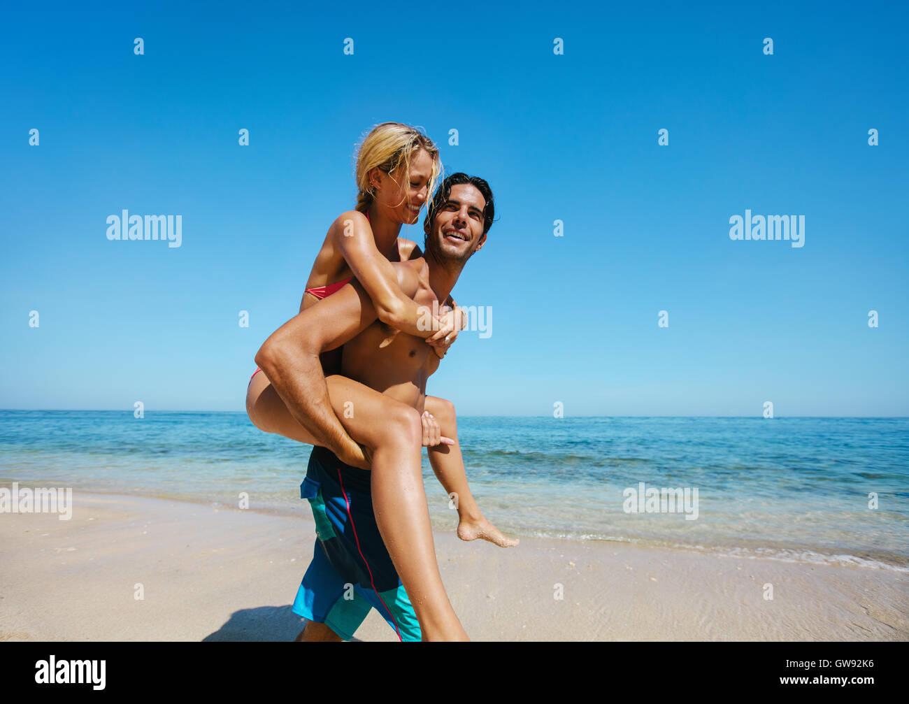Vista laterale shot di giovane che cura la sua ragazza sul retro in spiaggia. Giovane godendo piggybacking sulla Immagini Stock
