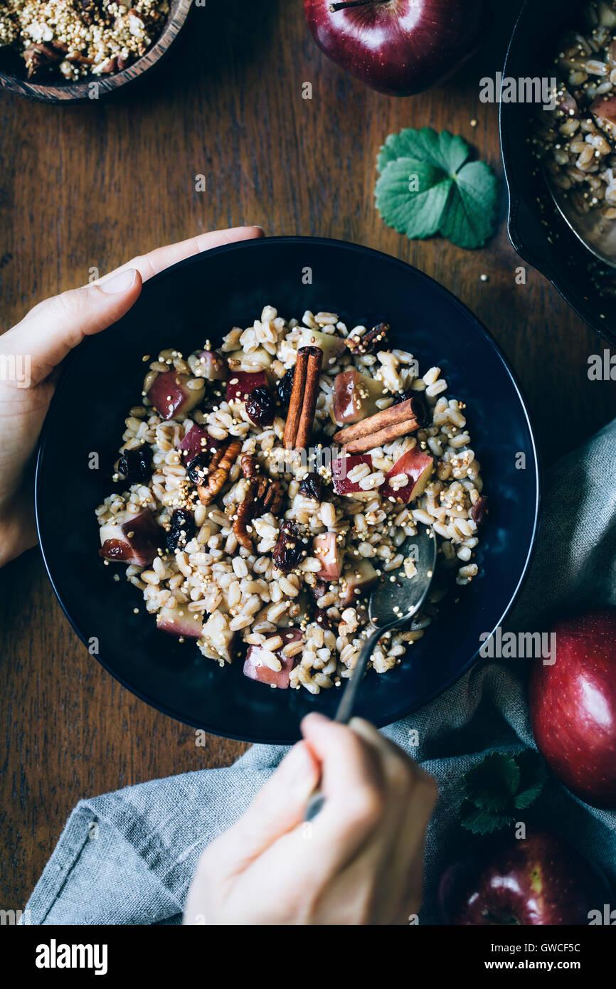 Un womans mani sono fotografate come lei sta per mangiare una ciotola di Farro calda colazione ciotola con cannella Immagini Stock