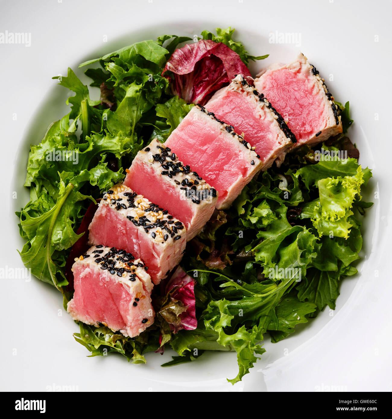 Tagliate a fette grigliate di bistecca di tonno in sesame su insalata verde vicino fino Immagini Stock