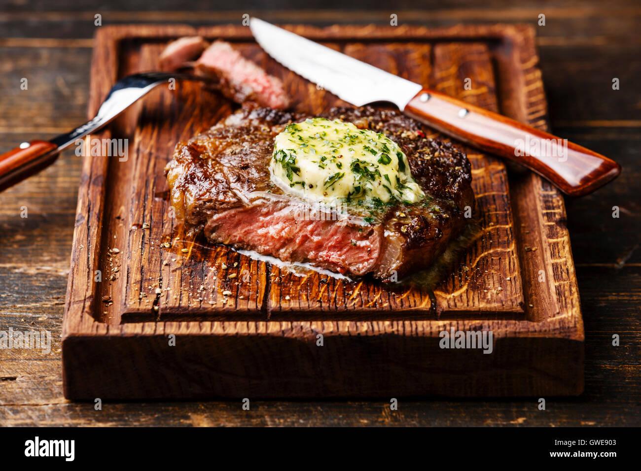 Grigliata di mezzo raro steak bistecca con burro alle erbe sul bordo di taglio Immagini Stock