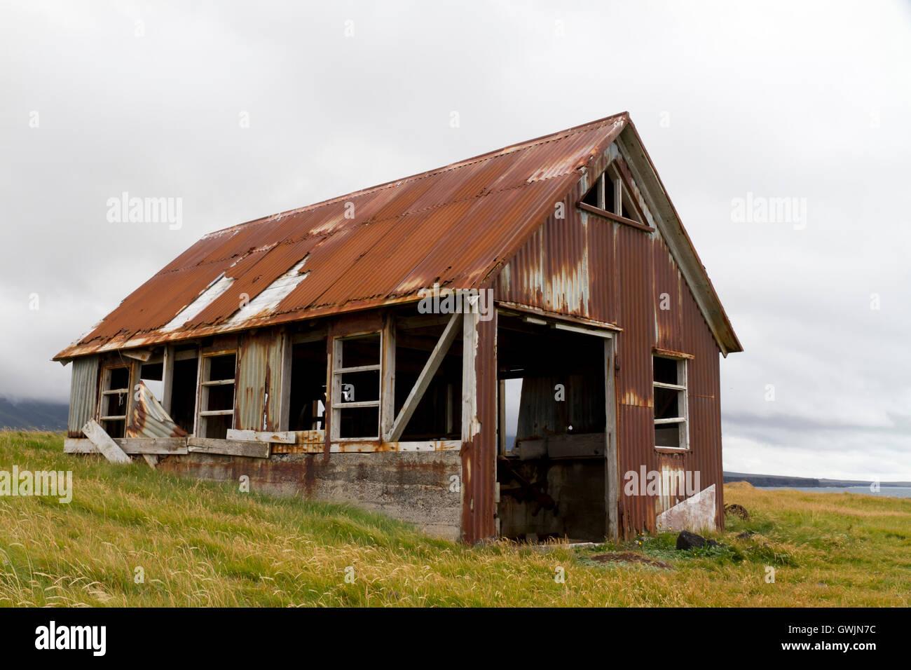 Scorrere verso il basso il vecchio capannone rivestita di rusty ferro corrugato, situato sulla costa Foto Stock