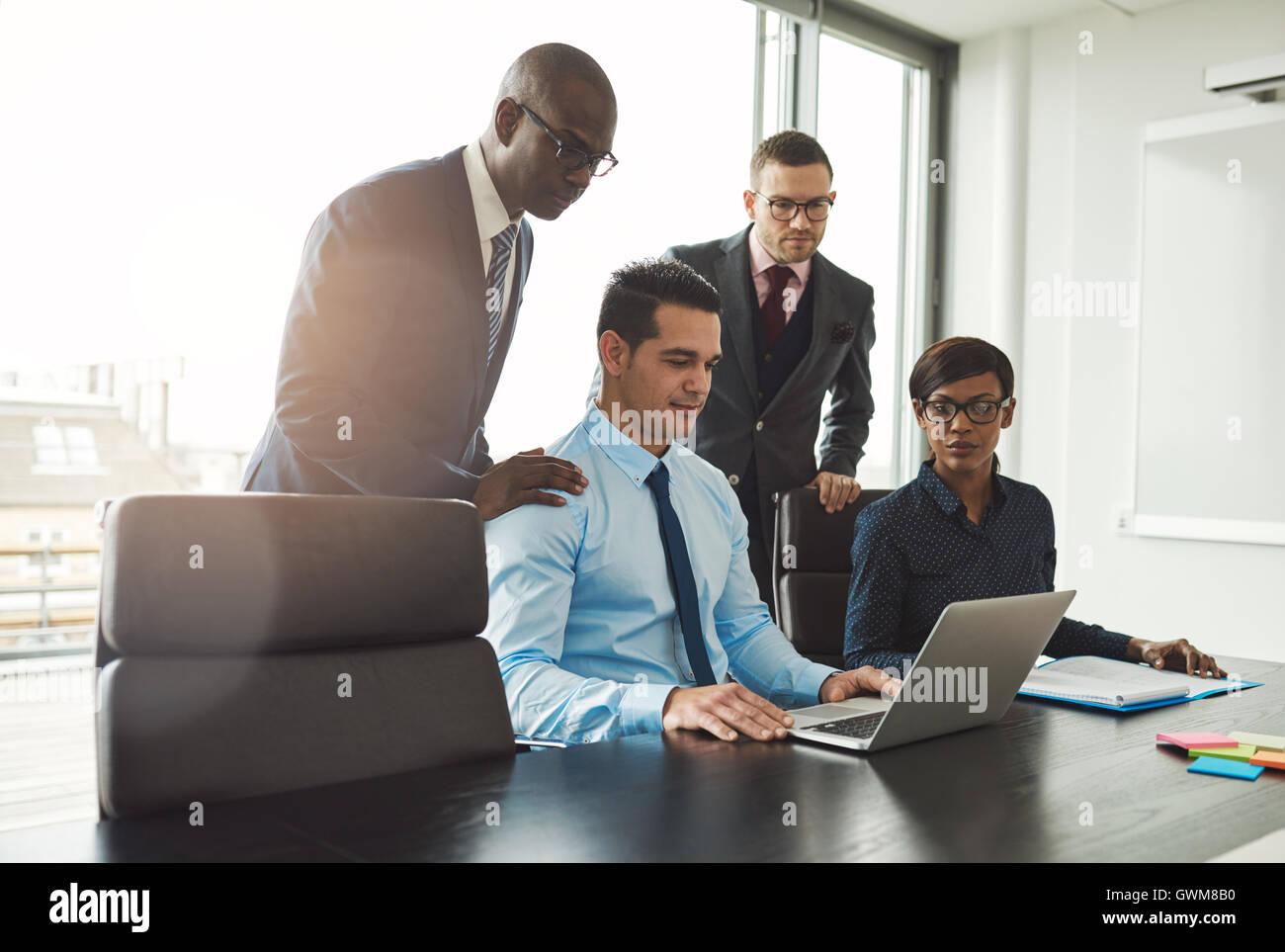Simpatico gruppo di diversi giovani uomini di affari in abbigliamento formale guardando sul computer portatile sul Immagini Stock