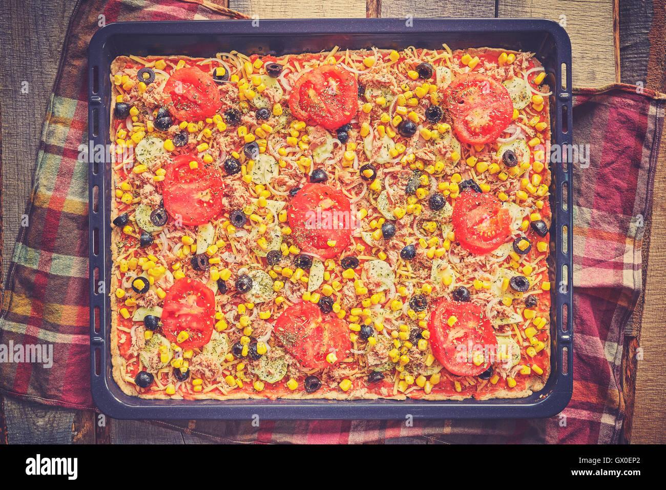 Vintage nei toni del tonno in casa la pizza con pomodori, olive, cipolla e mais pronto per cuocere su sfondo di Immagini Stock