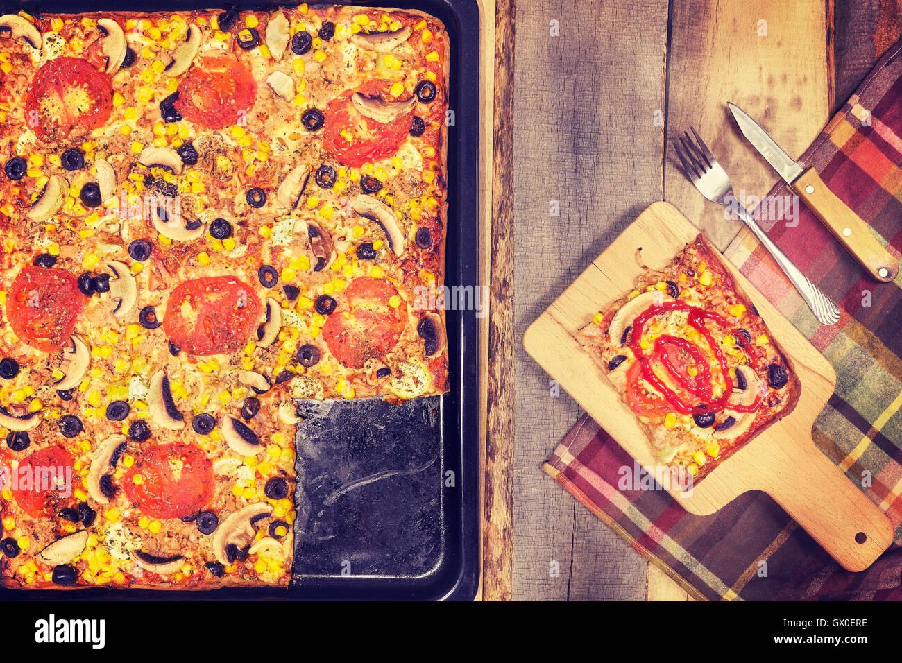 Vintage nei toni del tonno in casa la pizza con pomodori, olive, cipolla e mais su sfondo di legno, vista dall'alto. Immagini Stock