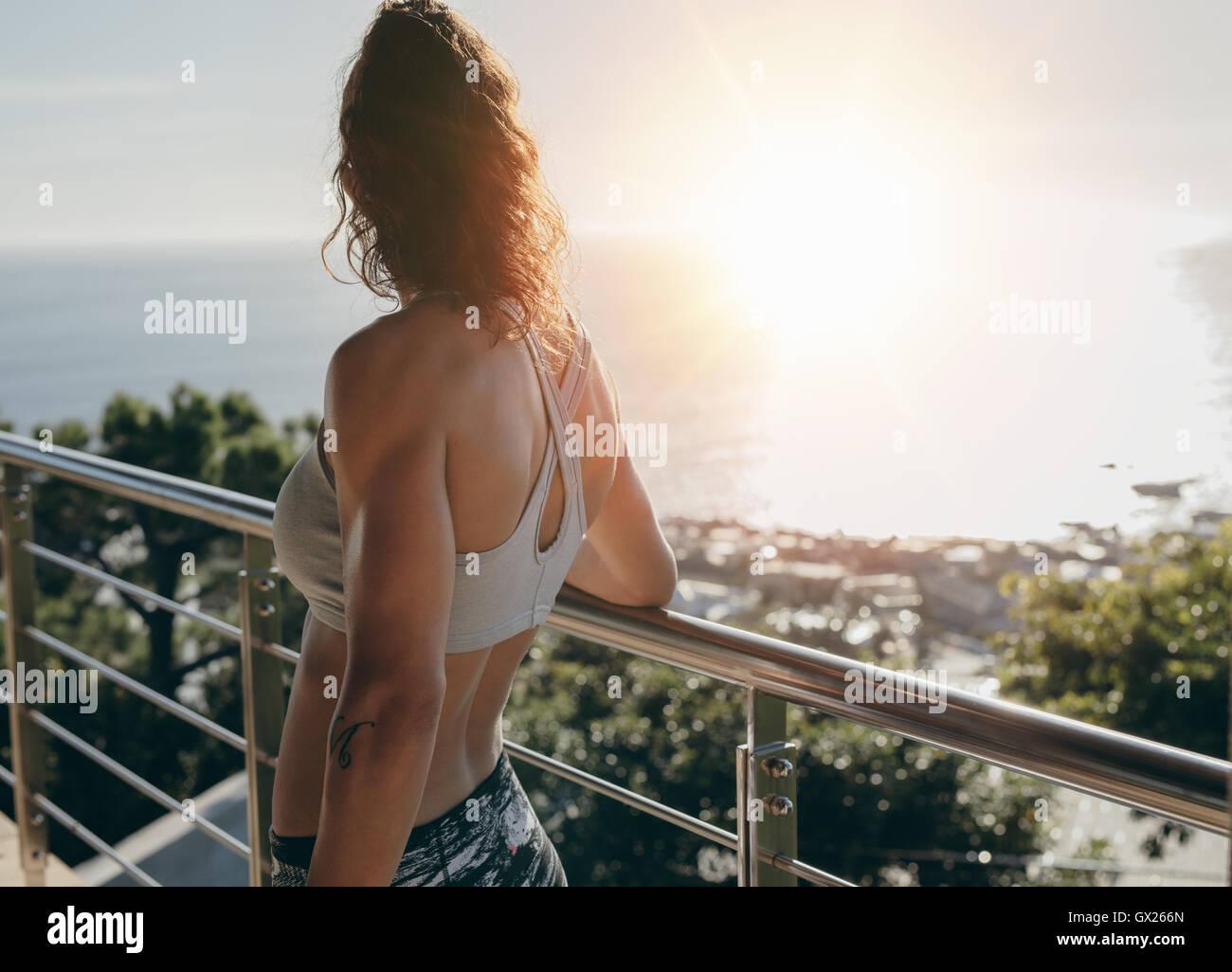 Vista posteriore del colpo di donna in piedi da una ringhiera di balcone e guardando lontano su una luminosa giornata Immagini Stock