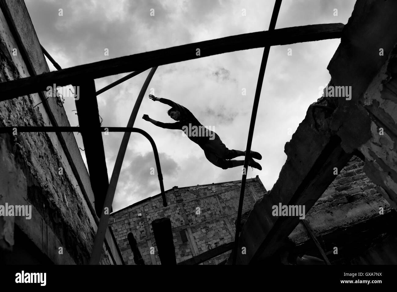 Un colombiano parkour runner salta sopra una intercapedine all'interno di una casa abbandonata durante la corsa Immagini Stock