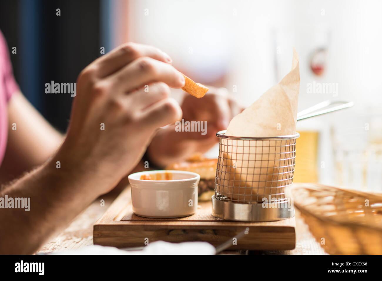 La mano del giovane uomo mangiare patatine in ristorante Immagini Stock