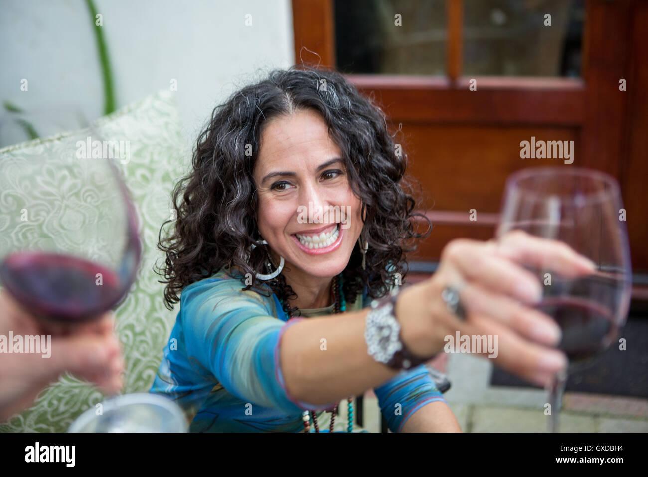 Sulla spalla vista di donne mature vino rosso toast al party in giardino Immagini Stock