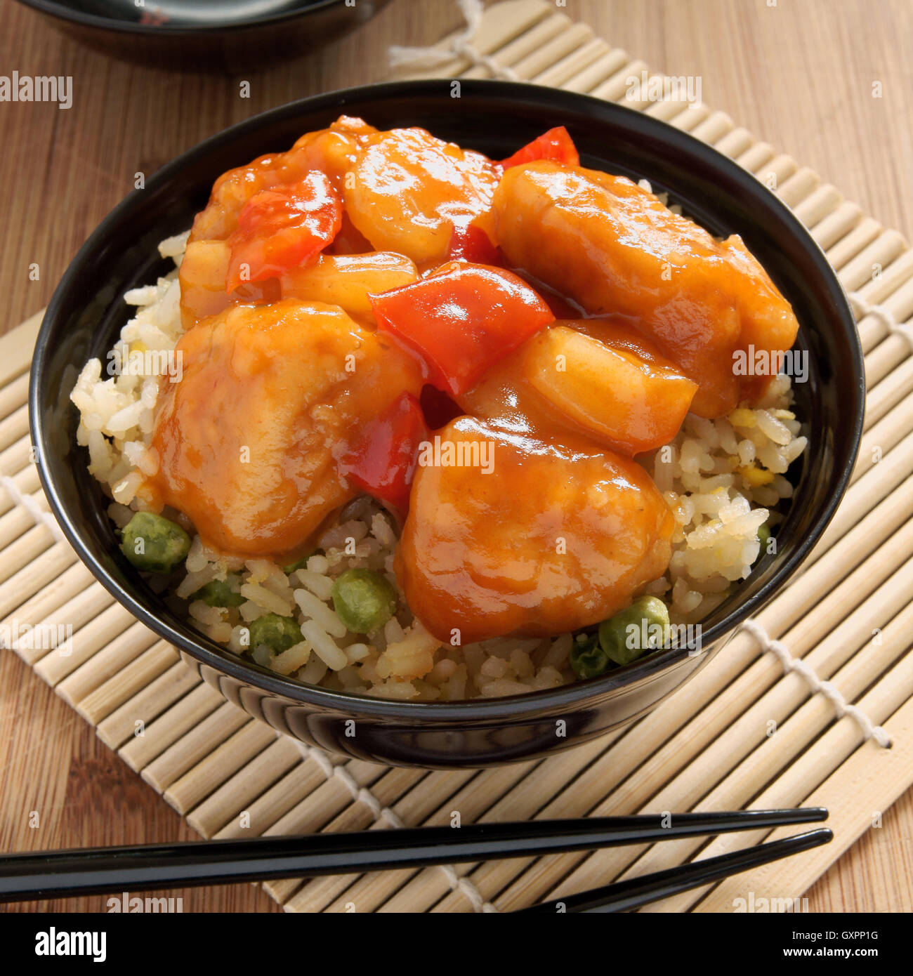 Dolce e aspro di pollo stile Cantonese con uovo fritto il riso in un recipiente di vernice con bacchette Immagini Stock