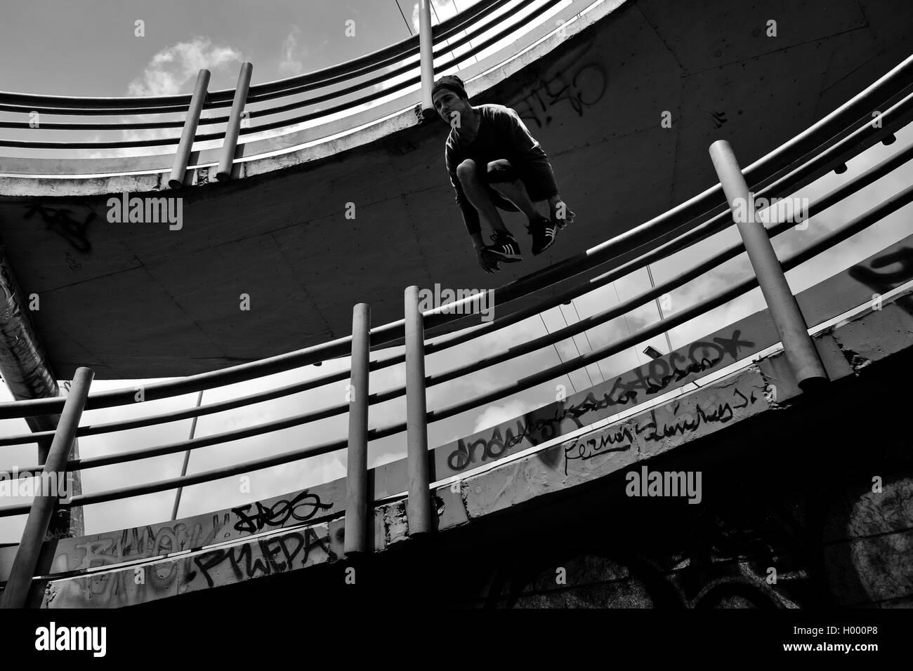Steven Mantilla, un parkour runner dal team Tamashikaze, salta sopra il cavalcavia della ringhiera di Bogotá, Immagini Stock