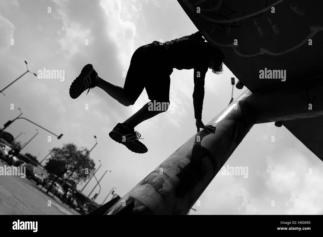 Steven Mantilla, un freerunner dal team Tamashikaze, esegue il parkour si sposta sulla passerella colonna di Bogotá, Immagini Stock