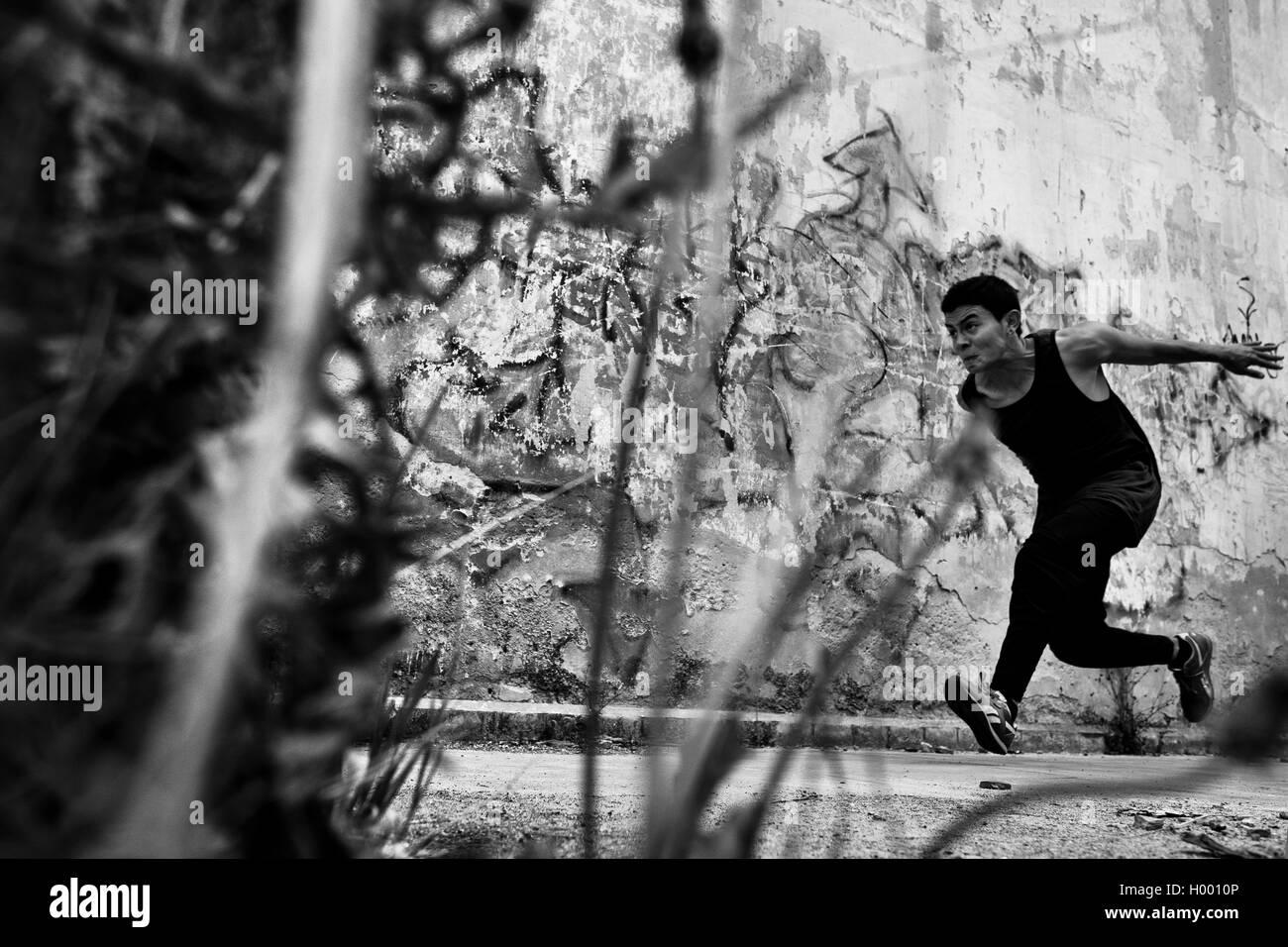 Un colombiano freerunner effettua un salto su un ostacolo durante il parkour sessione di formazione di Bogotá, Immagini Stock