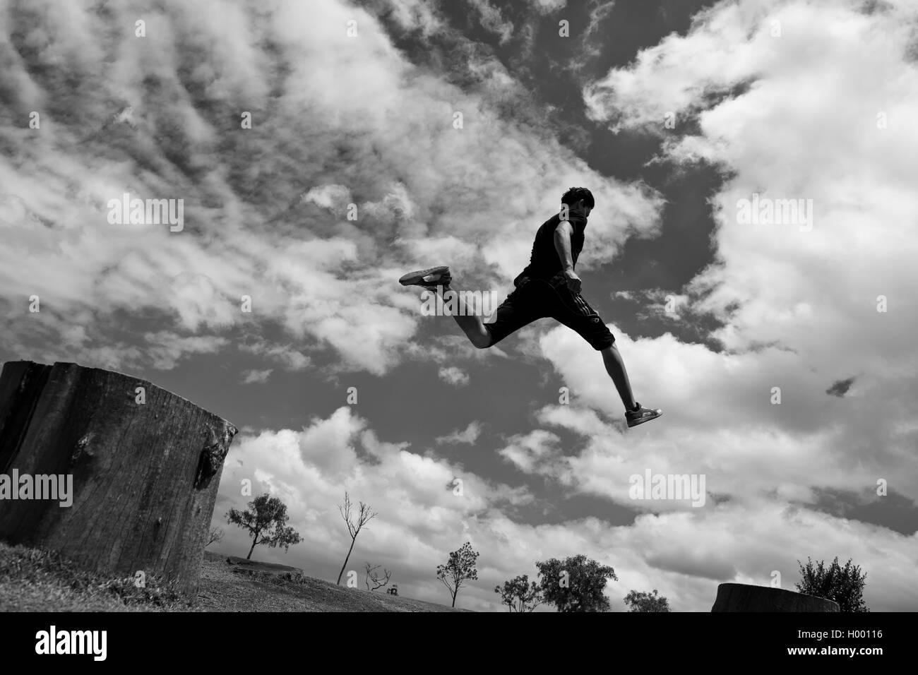 Un colombiano parkour runner esegue un salto in alto durante un funzionamento libero esercizio di formazione del Immagini Stock