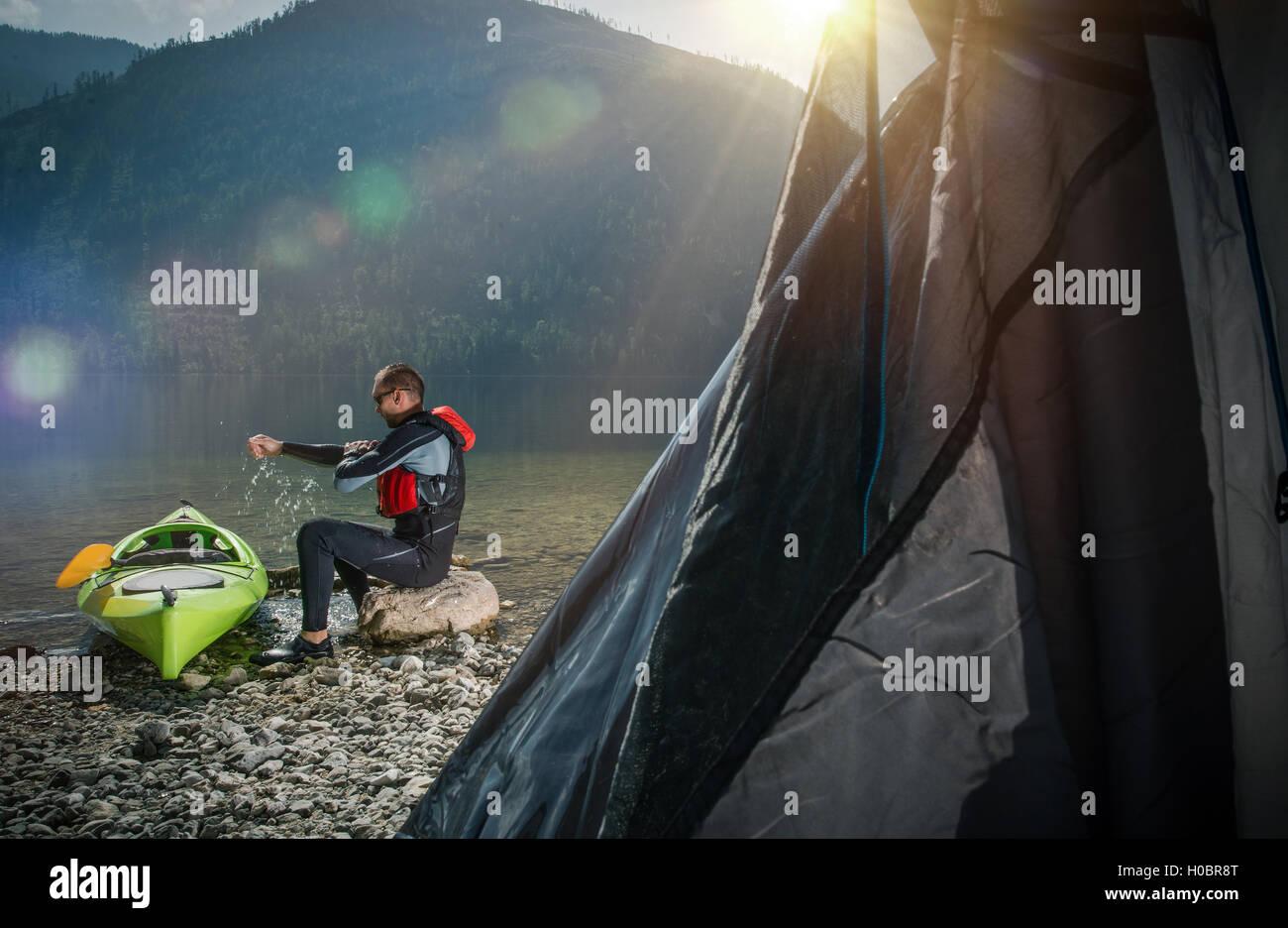 Il campeggio in riva al lago. Gli uomini il relax sul bordo del Lago di lato al suo Kayak. Immagini Stock