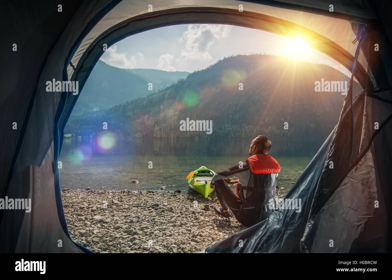 Attendamento e kayak sul lago. Sportivo caucasica Campeggio e kayak su Scenic Mountain Lake Shore. Immagini Stock