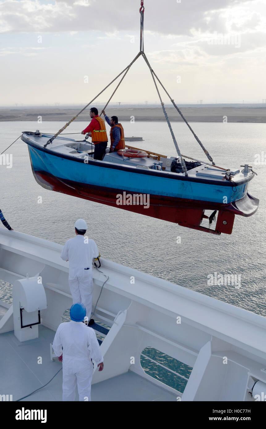 Una barca da pesca è sollevato fino a una nave da crociera Immagini Stock