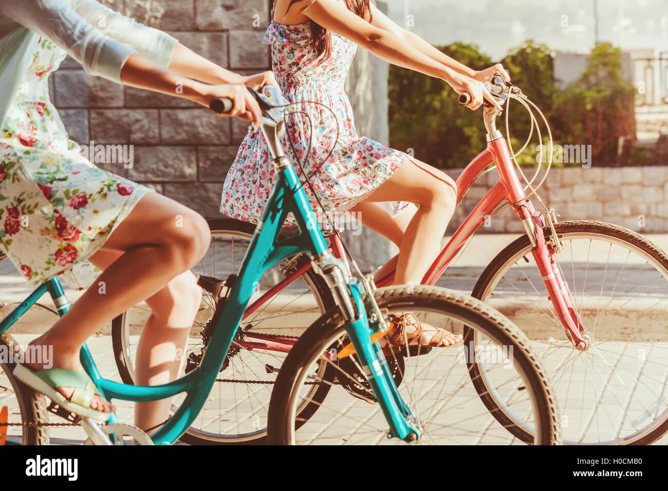 I due giovani ragazze con le biciclette in posizione di parcheggio Immagini Stock
