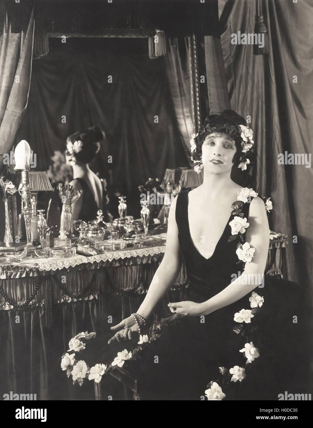 Ritratto di donna adornati con fiori seduti al tavolo Immagini Stock
