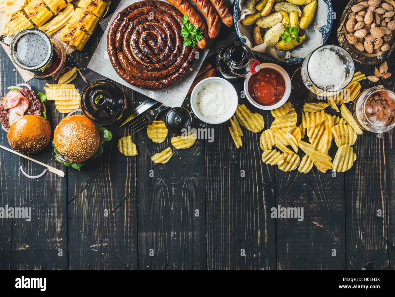 Birra e snack set. Oktoberfest cibo concetto di frame. Vatiety di birre, salsicce alla griglia, hamburger, mais, Immagini Stock