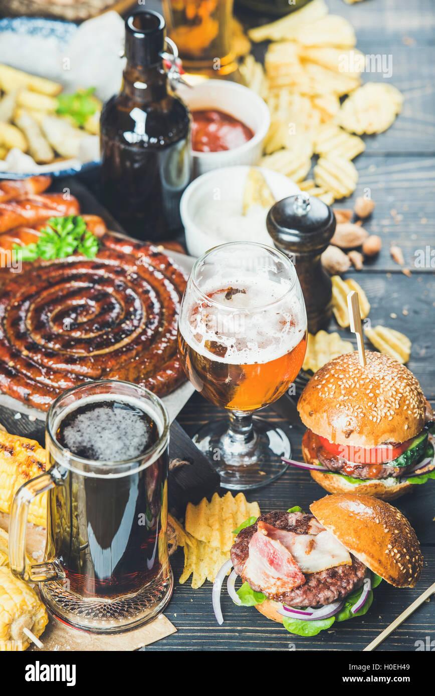 Birra e snack set. Oktoberfest cibo concetto di frame. Varietà di birre, salsicce alla griglia, hamburger, Immagini Stock