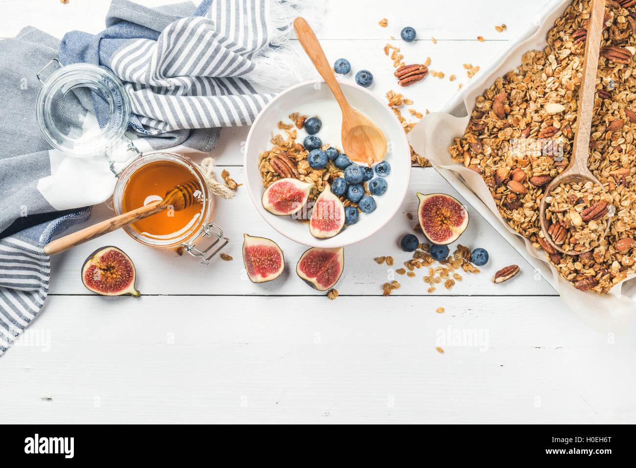 Sana colazione set. Oat granola con dadi, yogurt, miele, fichi freschi e mirtilli nella ciotola sul bianco sullo Immagini Stock