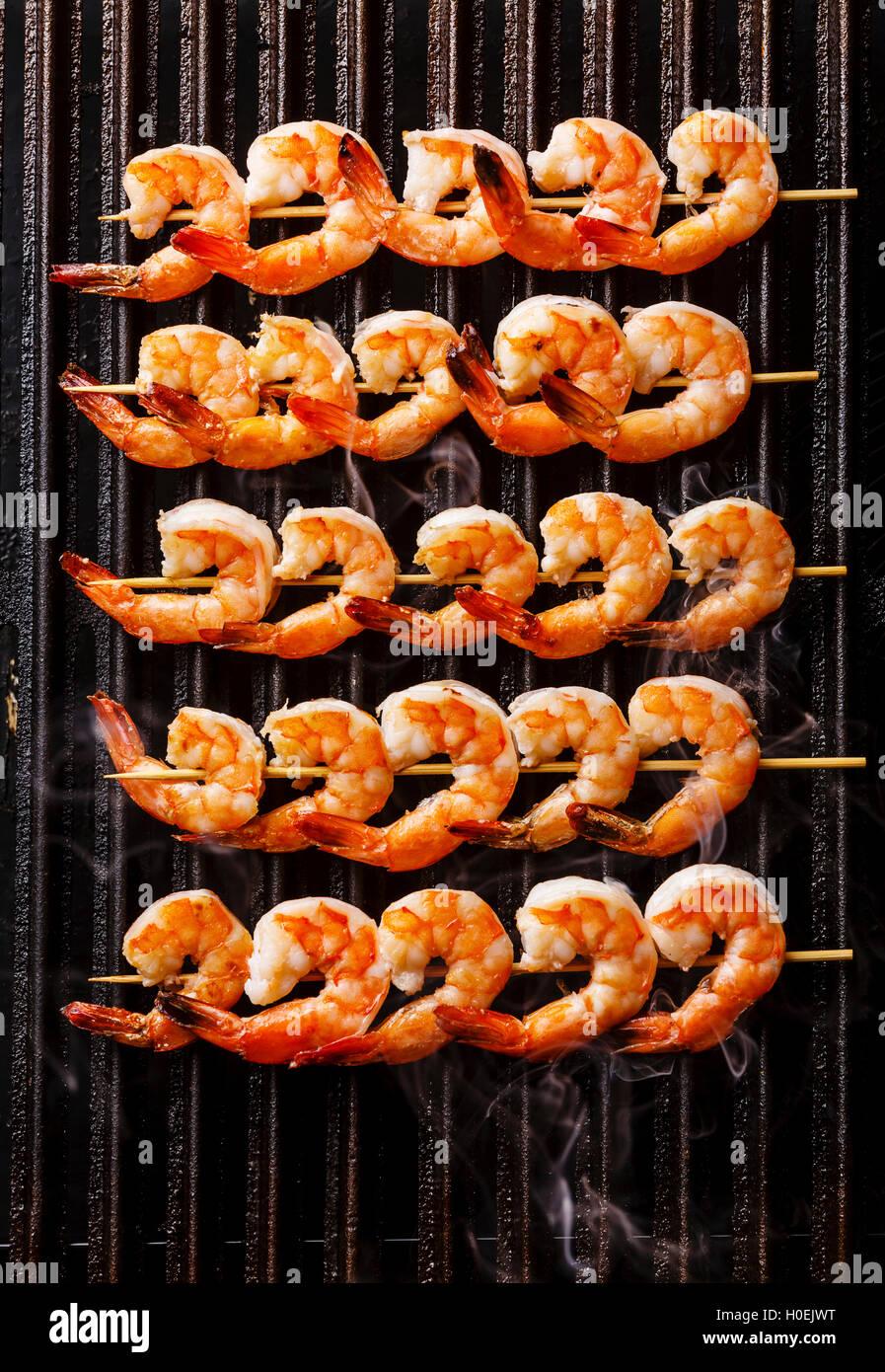 Grigliata di gamberi fritti su spiedini su ghisa nera sullo sfondo del grill Immagini Stock