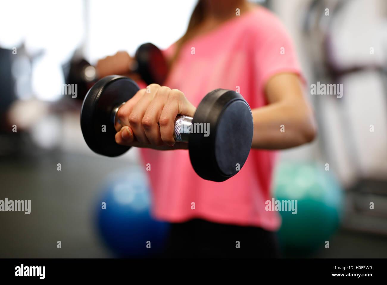 Donna al sport palestra fitness peso della formazione per la bellezza del corpo. Le ragazze di fitness con manubri. Immagini Stock