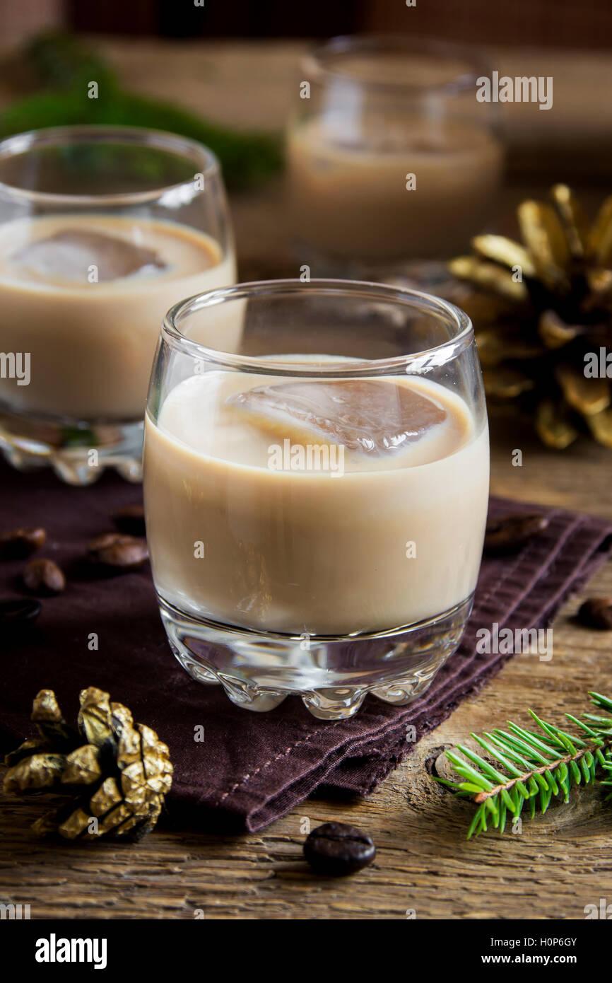 Irish cream liquore al caffè con ghiaccio, Natale ornamenti e decorazioni su legno rustico sfondo - festa in casa bevanda Foto Stock