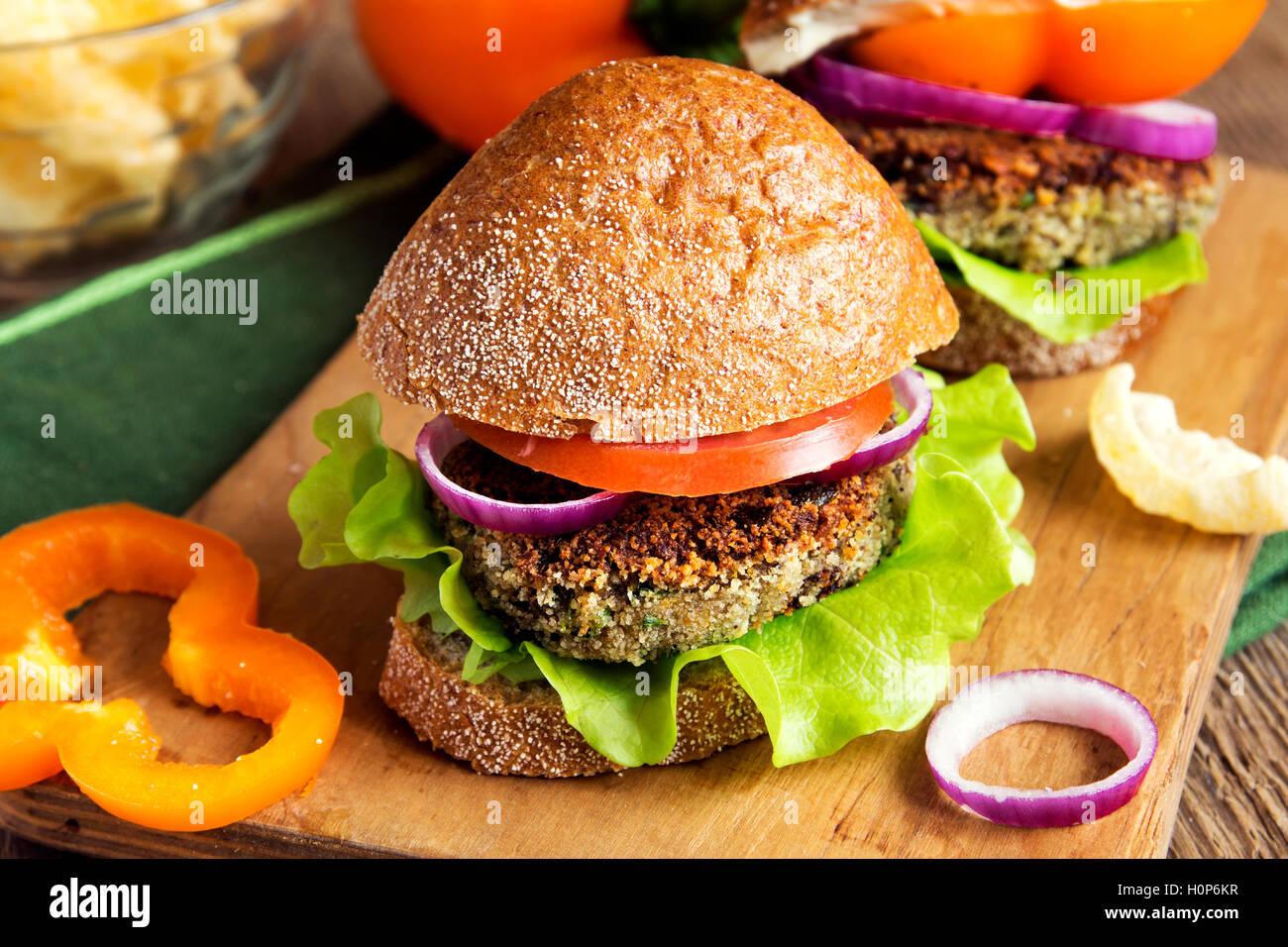 Vegetariano burger di lenticchie con verdure sul tagliere di legno - una sana gustosi snack vegetariano (Cibo, pranzo) Immagini Stock