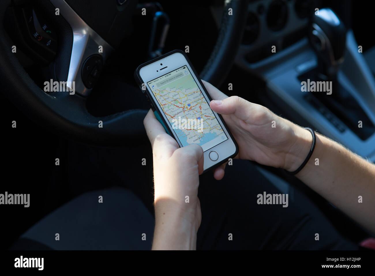 Giovane donna nella sua auto utilizzando il suo telefono 5s per controllare le indicazioni di guida Immagini Stock