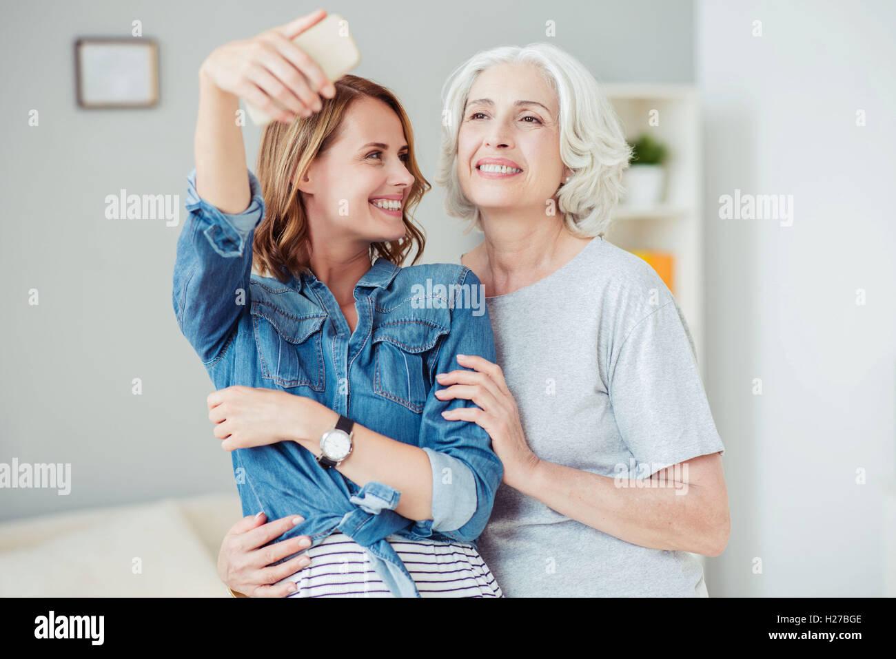 Positivo il piacere della donna e la sua madre facendo selfies Immagini Stock