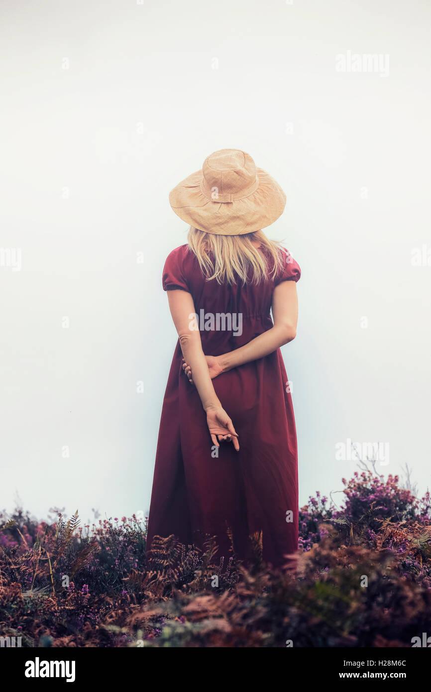 Una ragazza in un abito rosso è in piedi nel heather Foto Stock