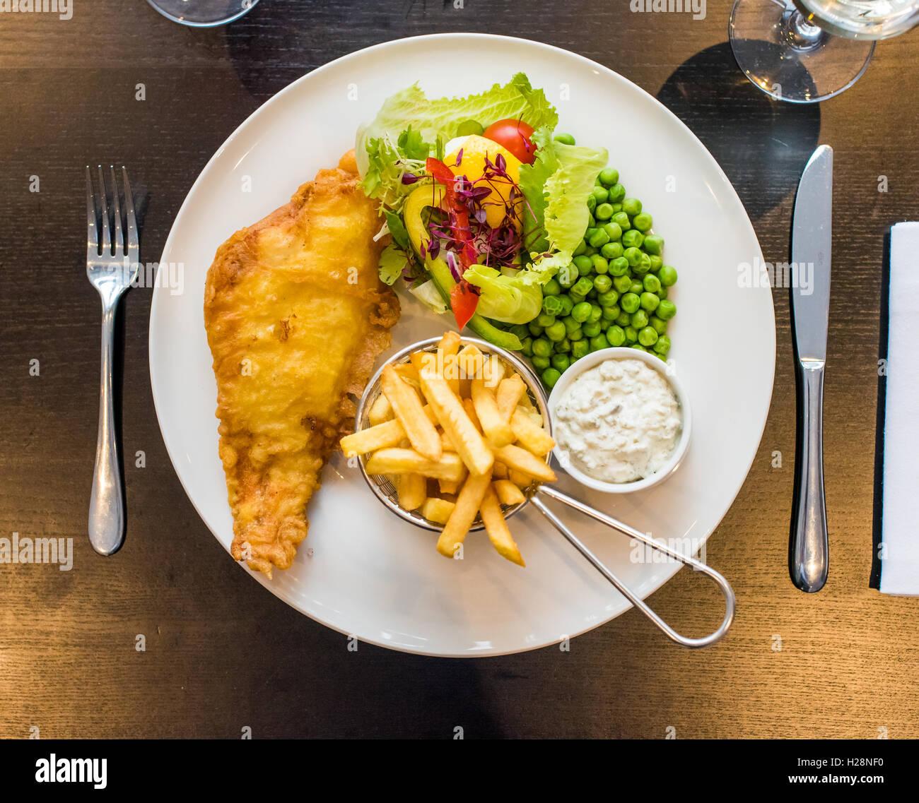 Pesce e patatine con piselli servito su una piastra con insalata e salsa tartara Immagini Stock