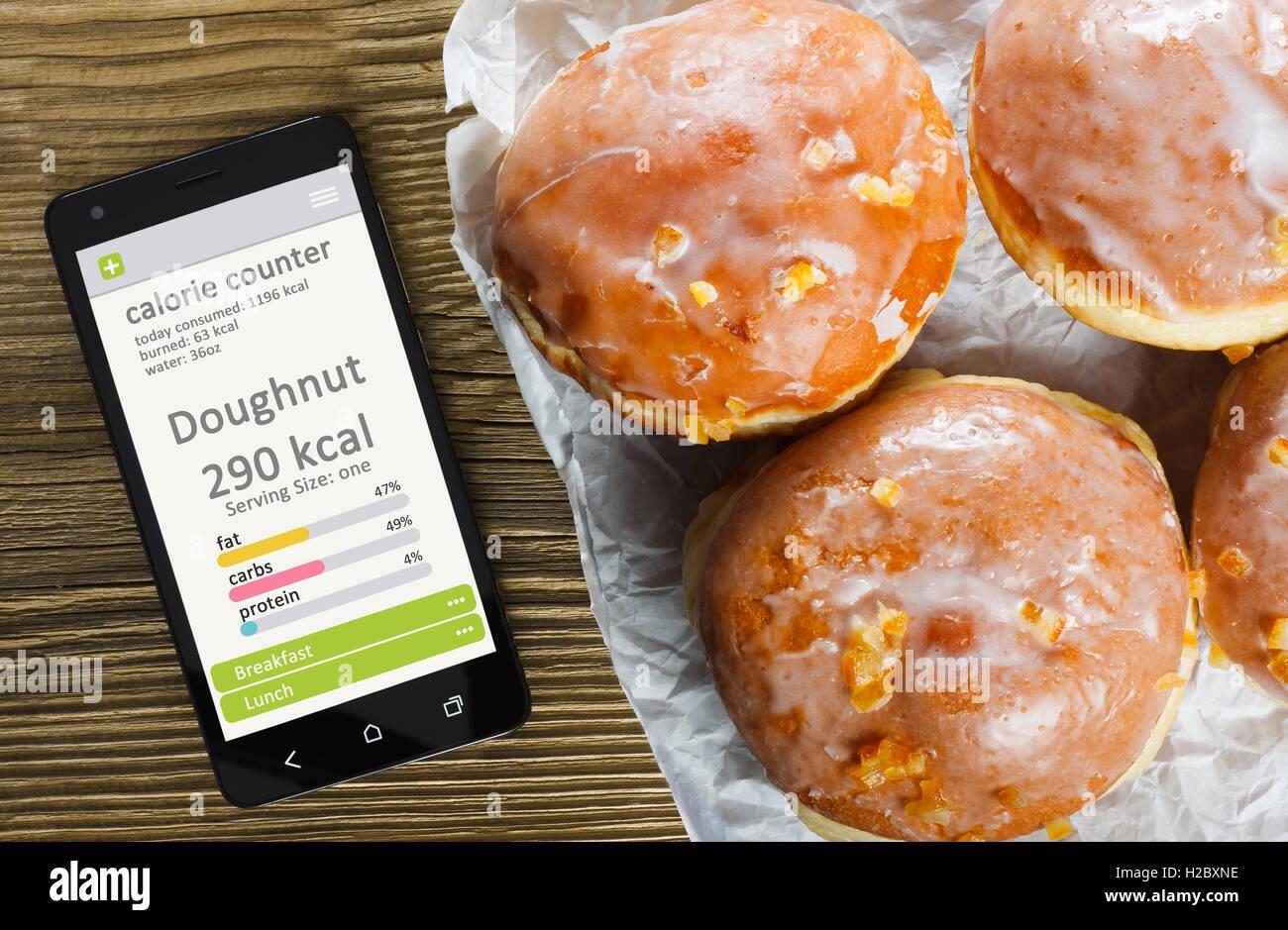 Calorie Counter concetto - telefono cellulare con contatore di caloria app sullo schermo e ciambelle. Tavolo in Immagini Stock