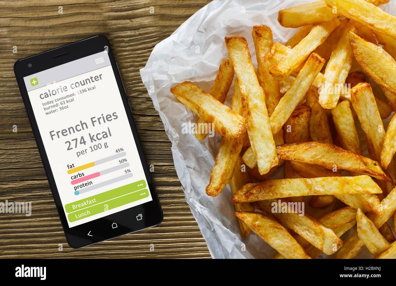 Calorie Counter concetto - telefono cellulare con contatore di caloria app sullo schermo e patatine fritte. Tavolo Immagini Stock