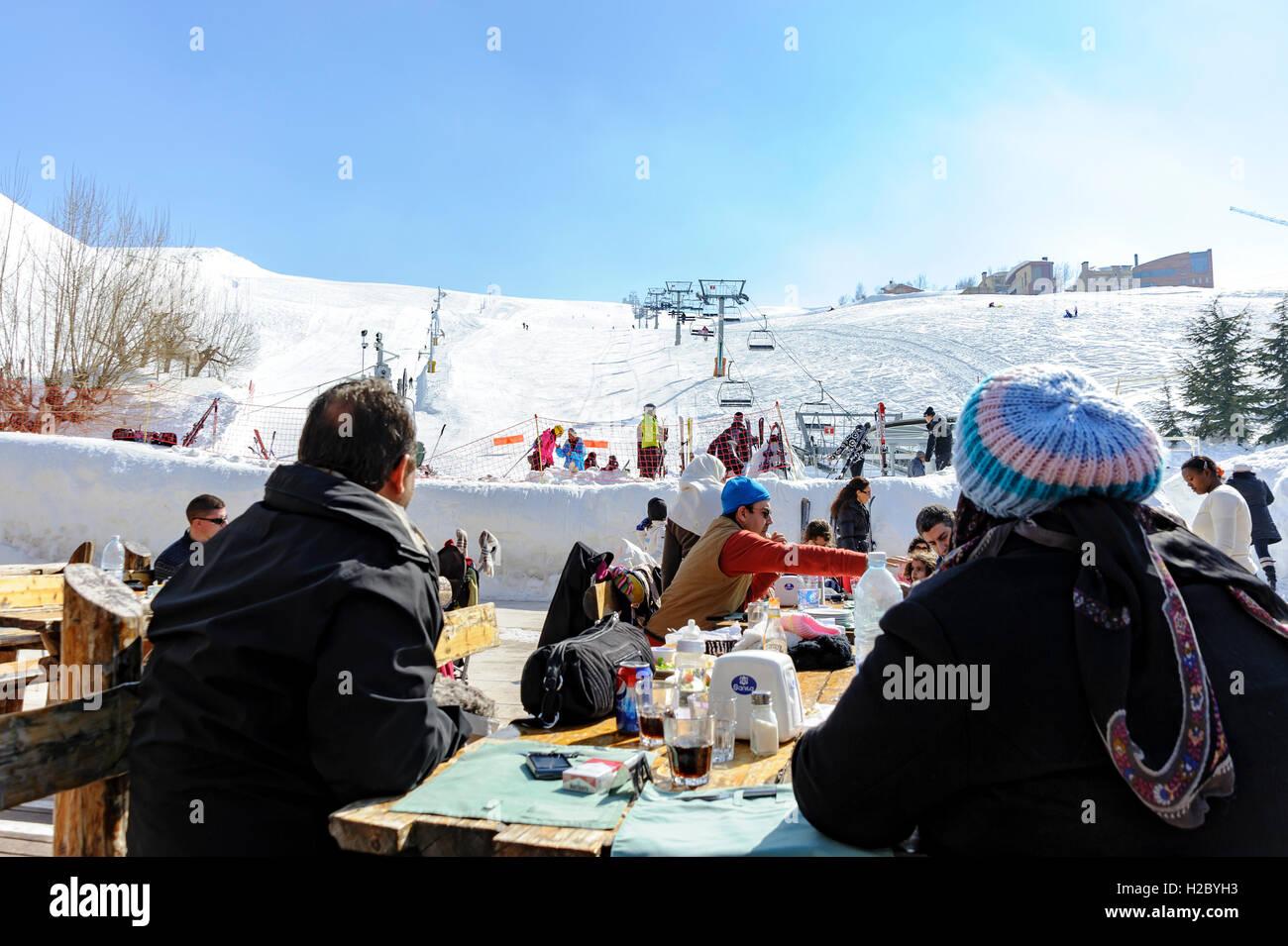 Persone mangiare e guardare gli altri a sciare a Kfardebian Mzaar (ex-Faraya) ski resort, Libano Immagini Stock