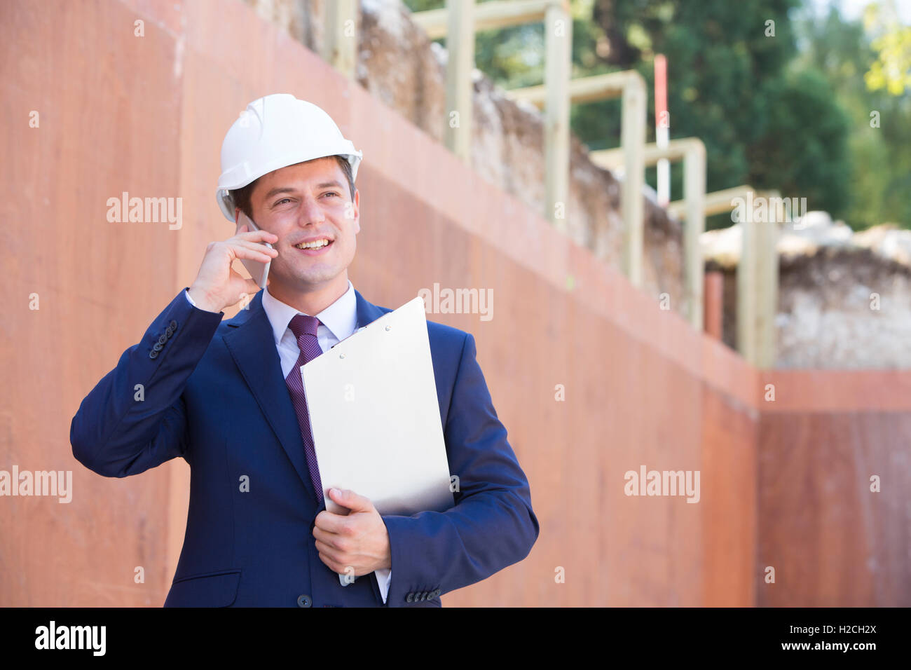 Architetto in cantiere utilizzando il telefono cellulare Immagini Stock