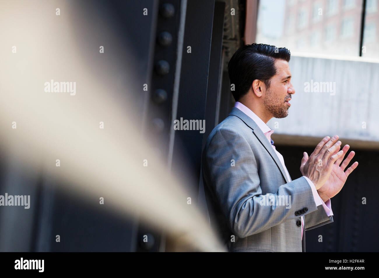 Imprenditore che indossa un abito grigio in piedi all'aperto, parlando e gesti con le mani alzate. Immagini Stock