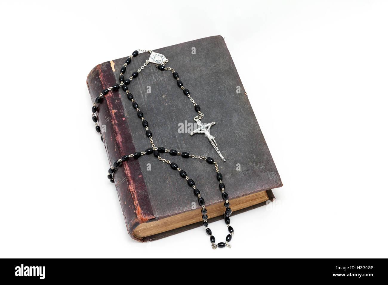 Libri antichi e il Rosario cattolico (grani di preghiera) (su sfondo bianco) Immagini Stock