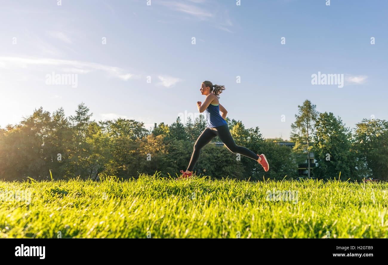 Giovane donna in abbigliamento sportivo a fare jogging nel parco, Monaco di Baviera, Baviera, Baviera, Germania Immagini Stock