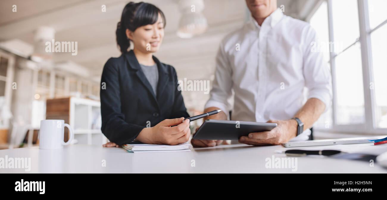 Colpo di giovani uomini di affari tramite digital dispositivo tablet pc al lavoro. Due giovani usando il touch screen Immagini Stock