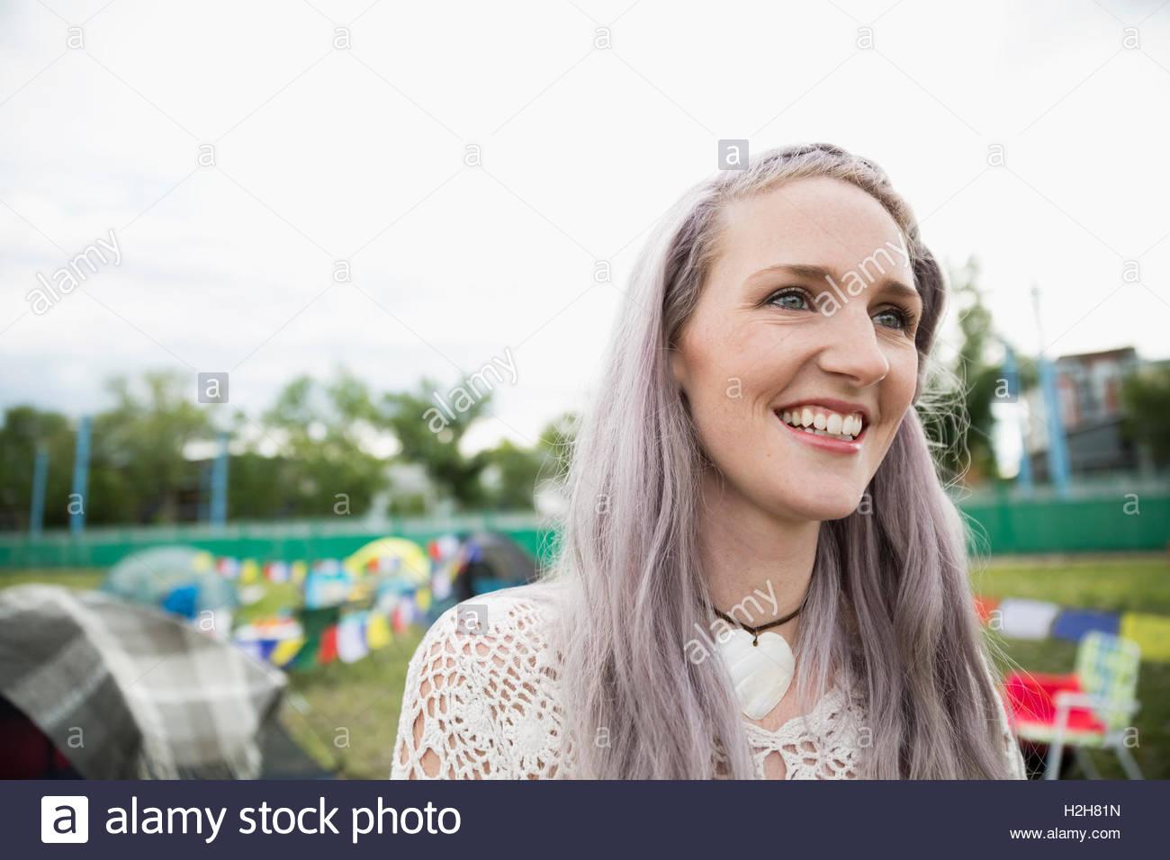 Ritratto sorridente giovane donna con chalk tinti capelli viola che guarda lontano al festival musicale estivo Campeggio Immagini Stock