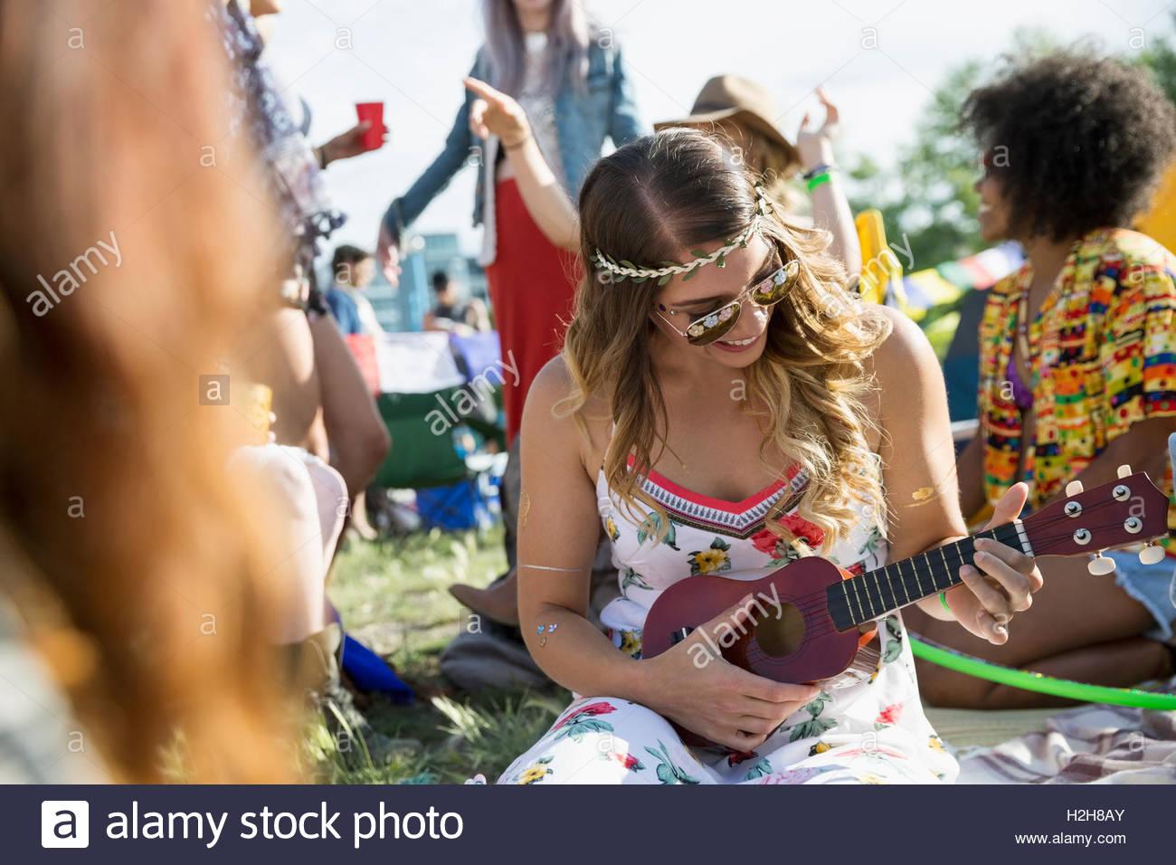 Giovane donna giocando ukulele al festival musicale estivo Campeggio Immagini Stock