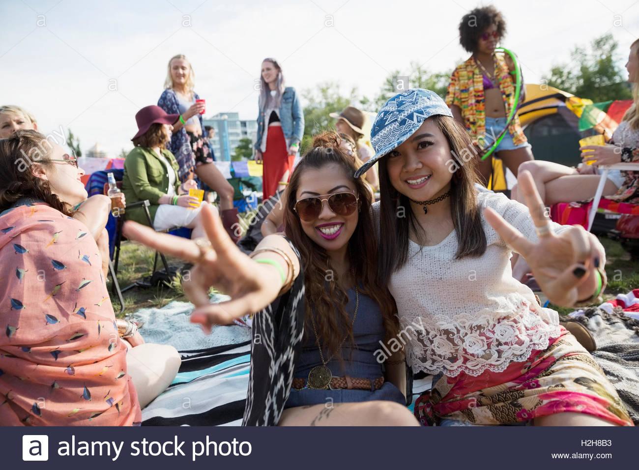 Ritratto entusiasta di giovani donne gesti segno di pace presso i festival estivi di musica Immagini Stock
