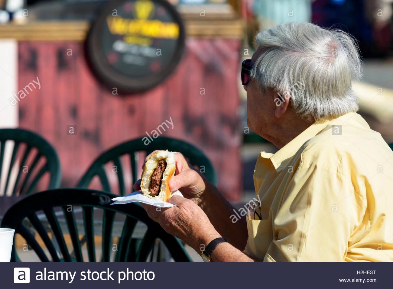 OAP mangiare un hamburger al mercato, Salisbury, Wiltshire, Inghilterra, Regno Unito Immagini Stock