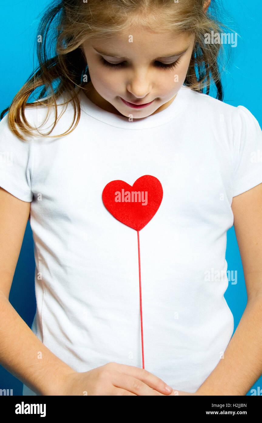 Bambina tenendo a forma di cuore su un bastone, il concetto di amore Immagini Stock