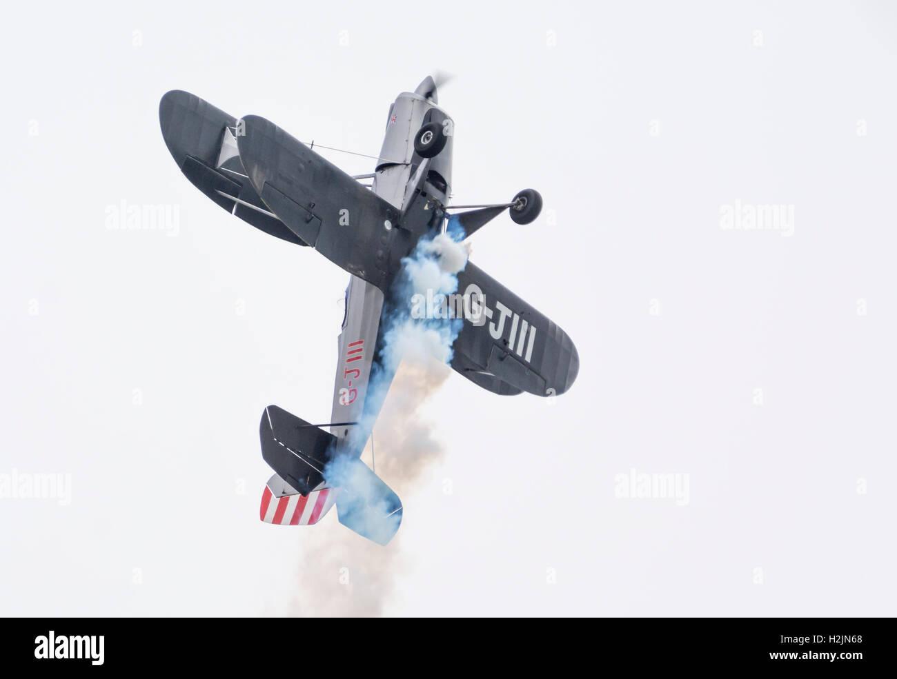 Arrampicata biplano con fumo proveniente da esso. Aeromobile è G-J111 monoposto a singola elica biplano. Immagini Stock