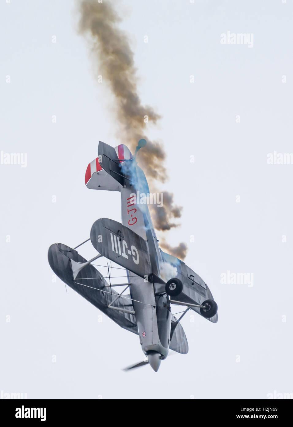 Diving biplanare verso il suolo con fumo proveniente da esso. Vedere la descrizione per maggiori informazioni. Immagini Stock