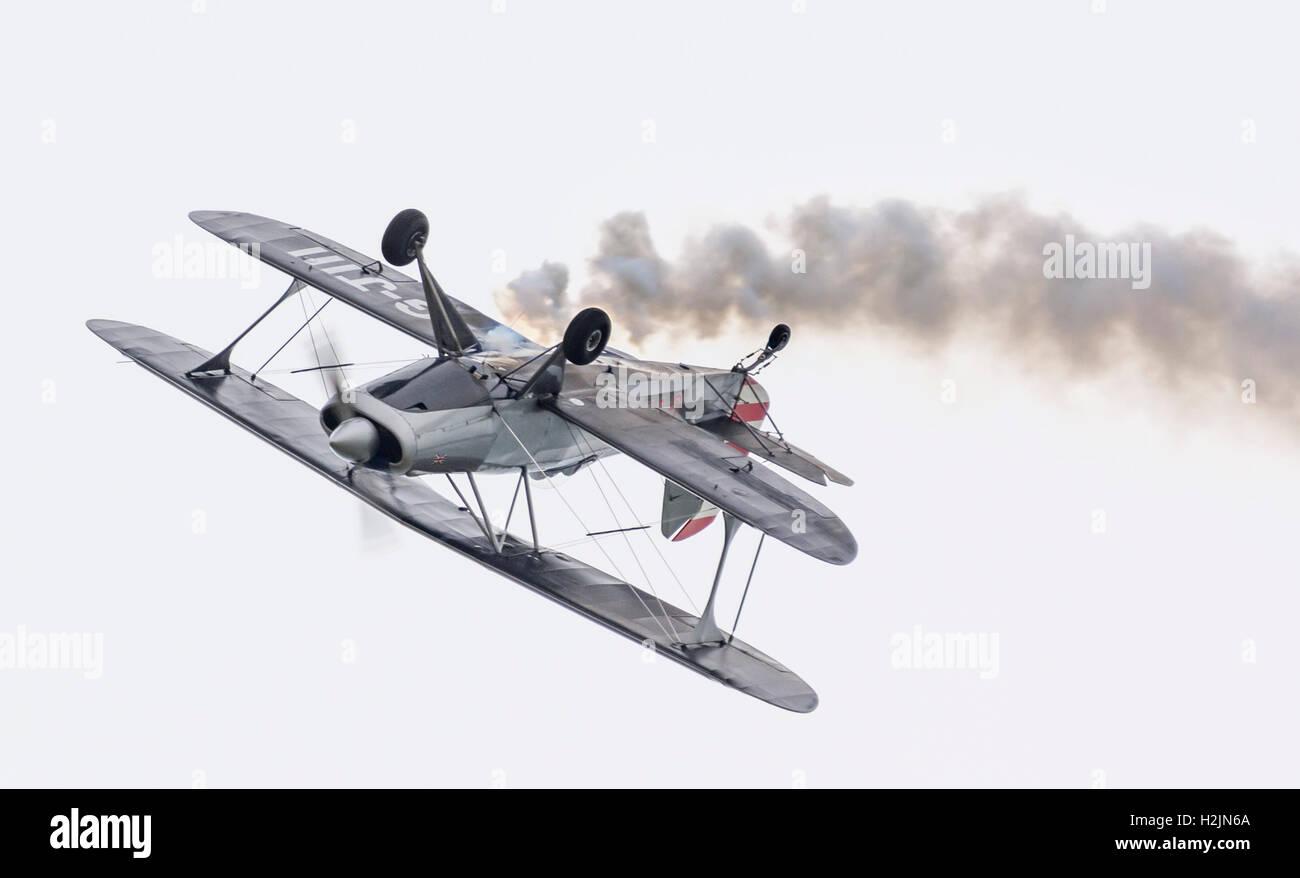 Un biplano capovolta la pratica per un display dell'aria. Aeromobile è G-J111 monoposto a singola elica Immagini Stock