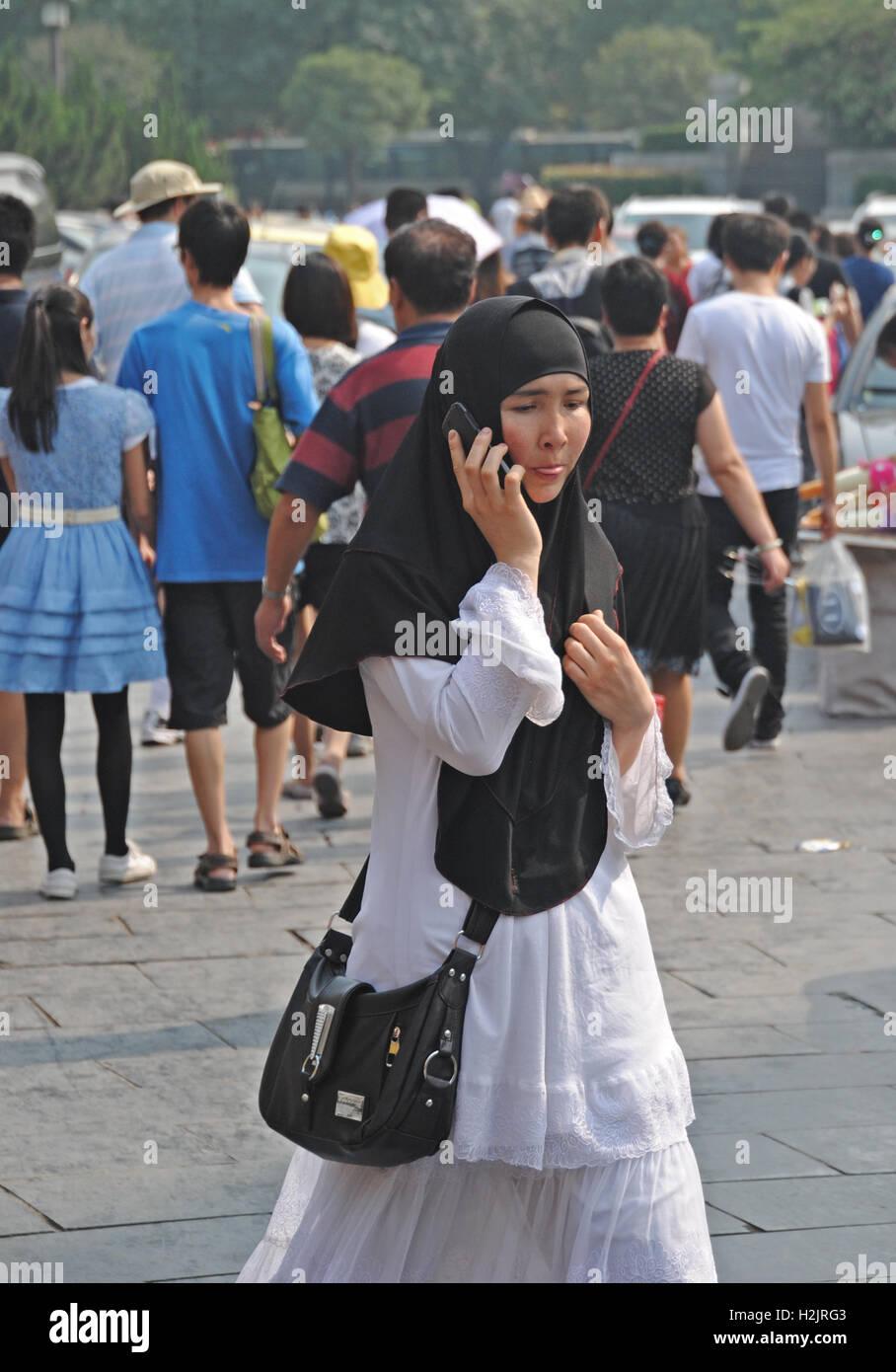 Un Cinese ragazzina musulmana che indossa il suo copricapo prende una chiamata come lei cammina attraverso Xian, Immagini Stock